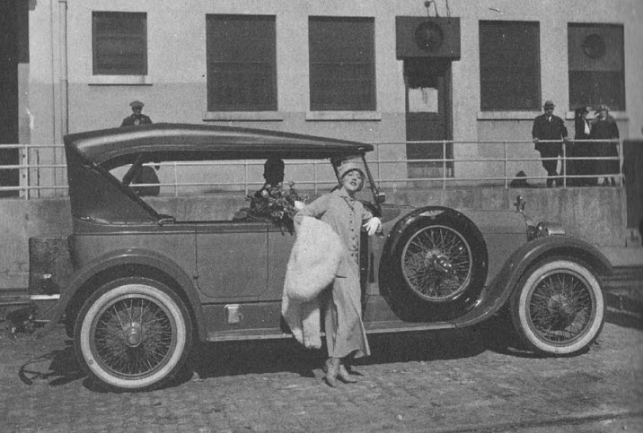 Mae strikes a pose at the studio with one of her automobiles.